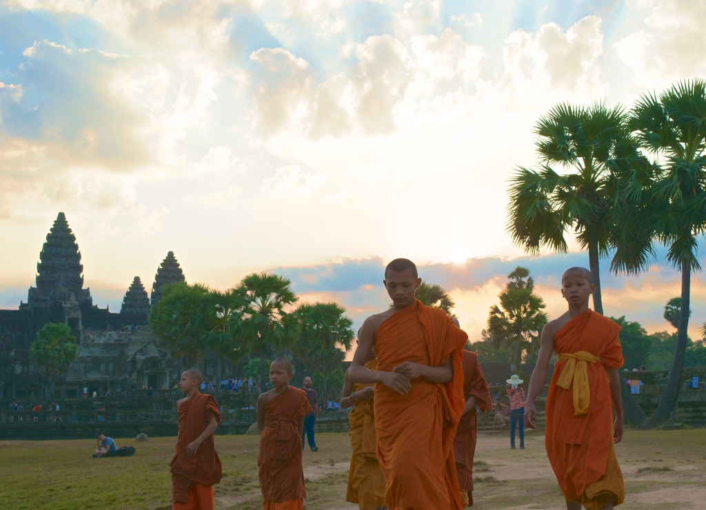 A young group of Buddhists at sunrise at Angkor Wat